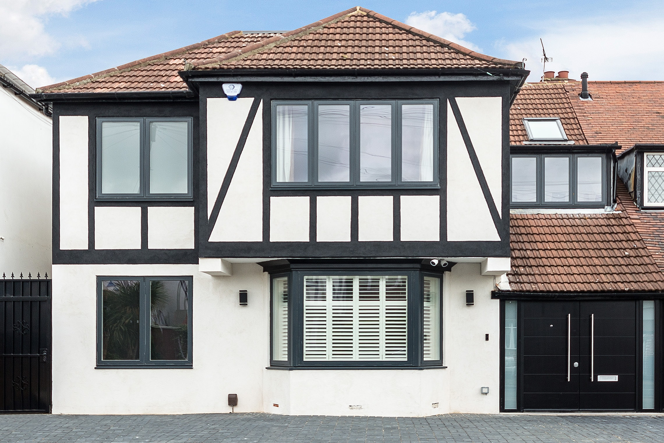 house-extension-gantshill-facade-double-front-door-white-render-black-details