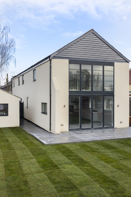 Construction_Victorian_building_conversion_exterior_rear_facade_porcelain_tiles_patio_glass_doors_window_krender_lawn_garden_grass_timber_cladding_patio_scaled-minå